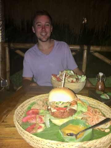 Enjoying tempeh burger at Galanga in Amed Bali with a friend